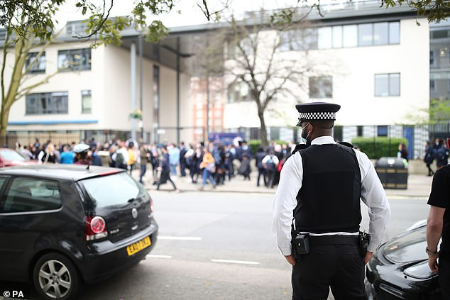 Pictured: A police officer outside Pimlico Academy School, west London, where students staged a walkout in protest over a school uniform policy that they claim is discriminatory and racist. Picture date: Wednesday March 31