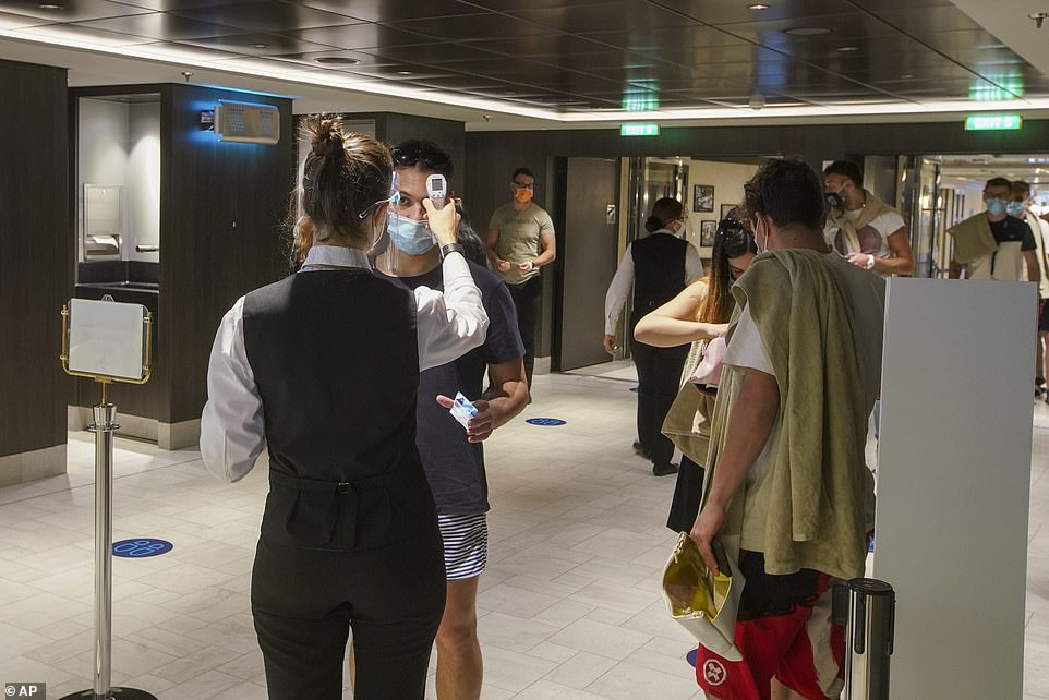 Passengers are closely monitored to prevent an outbreak of COVID-19 (pictured, passengers have their body temperature measured before they enter one of the ship's restaurants)