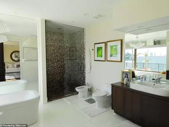 The modern furnished bathroom is brightly lit thanks to some large windows and mirrors that back onto the water