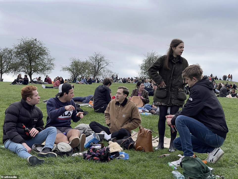 Hundreds of people gathered on Primrose Hill yesterday as restrictions eased this week allowed them to meet outside. Pictured: People wear coats as they sit on the hill together