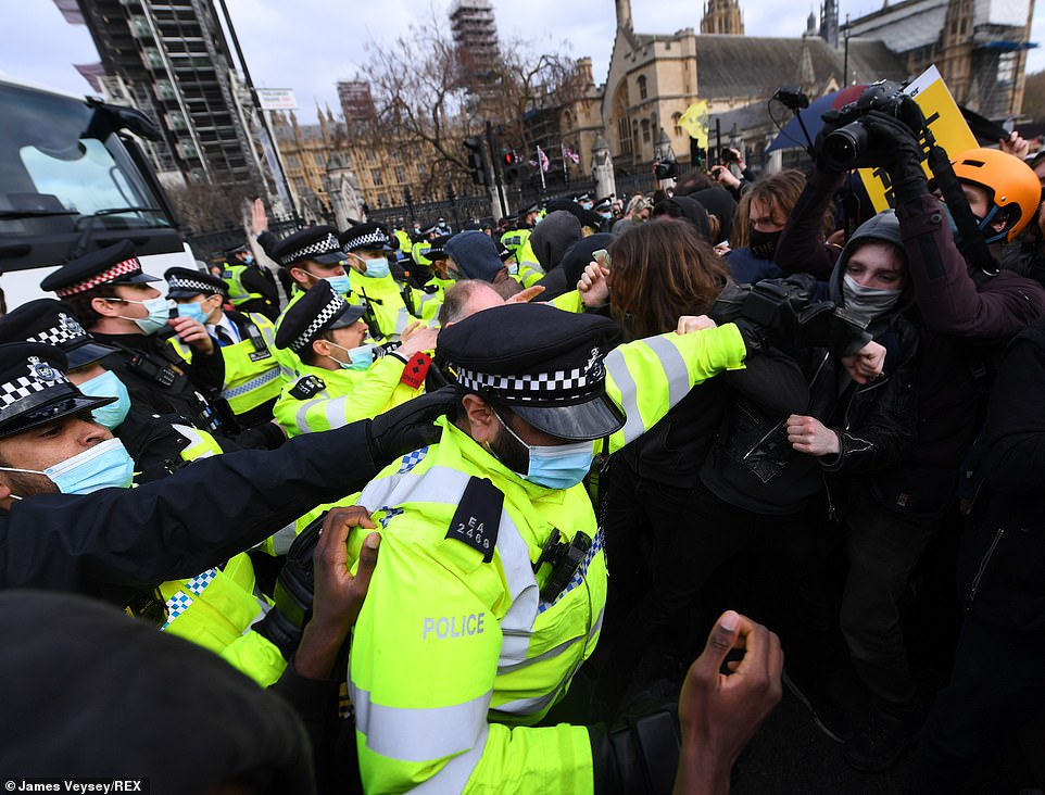 Protestors and police officers pictured in Parliament Square, central London, during today's Kill the Bill protest. Projectiles were thrown as police pushed protesters away and at least one officer was injured in the scuffle