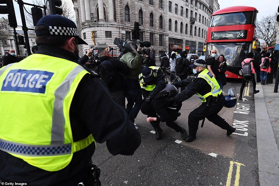 Police confront protestors with a bus seen in the background during a Kill the Bill demonstration on Saturday in London