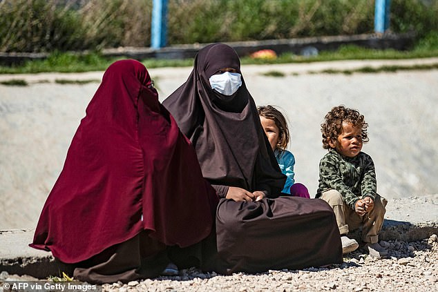 A woman sits with her child on the ground at Camp Roj, where relatives of people suspected of belonging to the Islamic State (IS) group are held, in the countryside near al-Malikiyah (Derik) in Syria's northeastern Hasakah province, on March 28, 2021