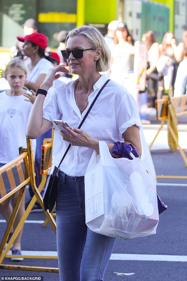 All smiles:In her left hand, the doting mother carried a haul of showbags and chocolates in a bag for her children