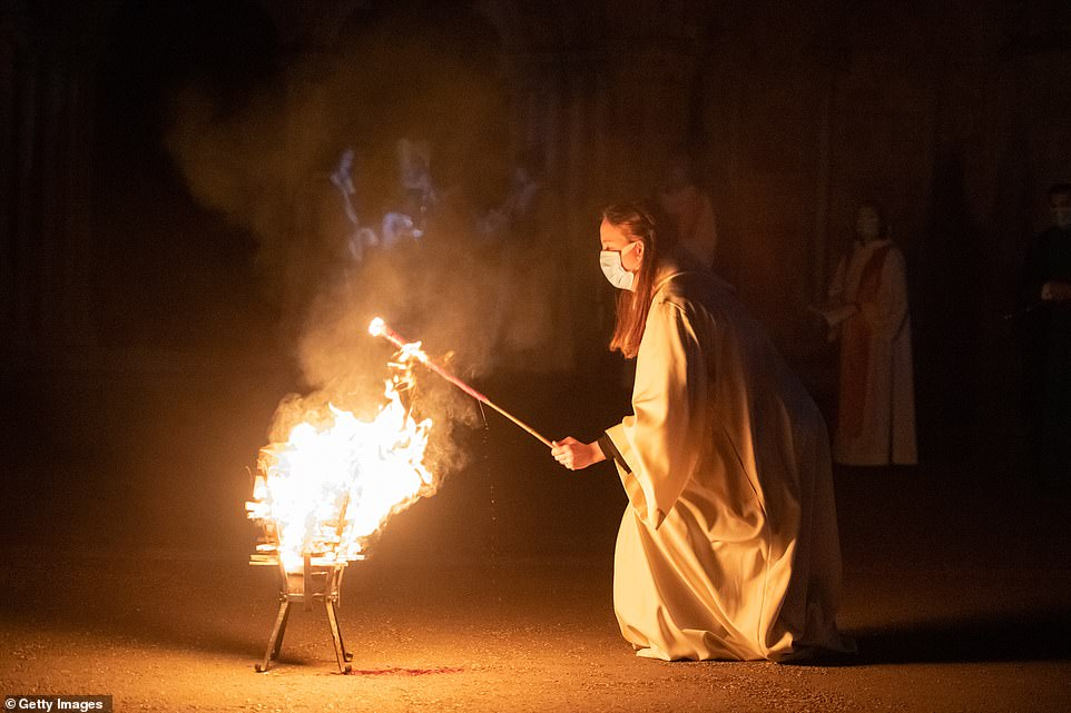 A fire in the brazier is used to light a wick for the Paschal candle at Salisbury Cathedral in England during a socially distanced ceremony