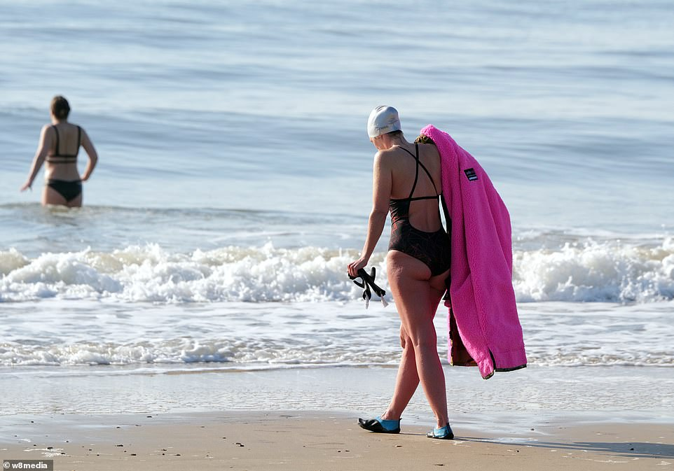 Two women are seen taking the plunge in Sandbanks on a sunny but crisp feeling Easter Sunday morning