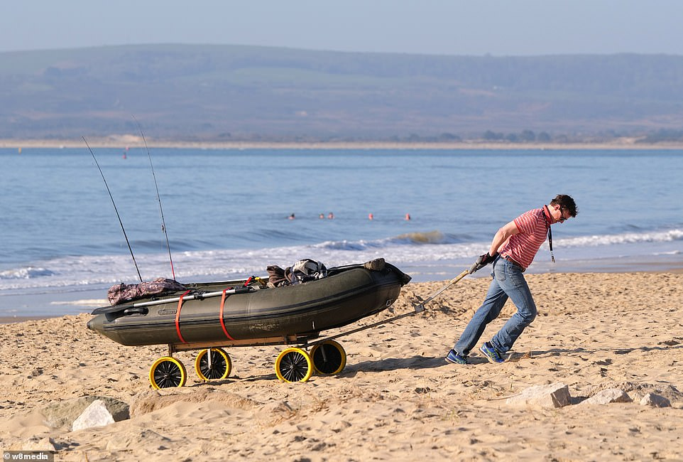 A man is seen pulling his rubber dingy from the water in Sandbanks, Dorset. Swimmers can be seen braving the water behind