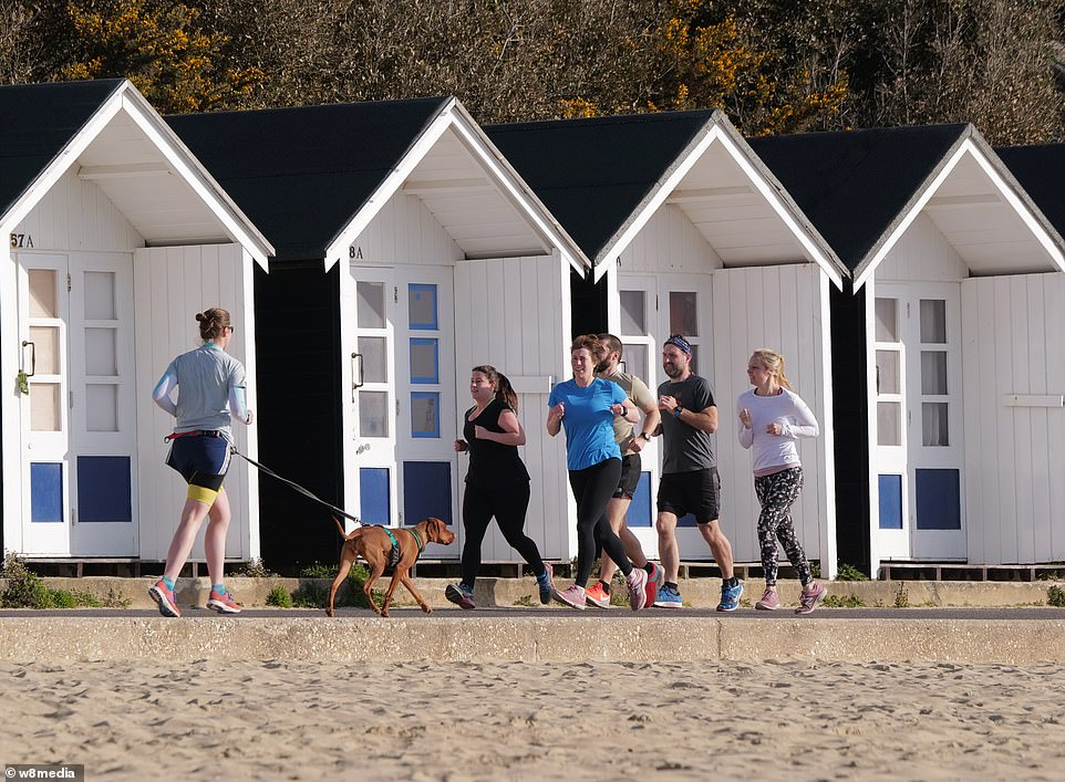 Runners enjoy the sun in Sandbanks, Dorset, where hundreds have taken to the beach to soak up the Easter Sunday rays