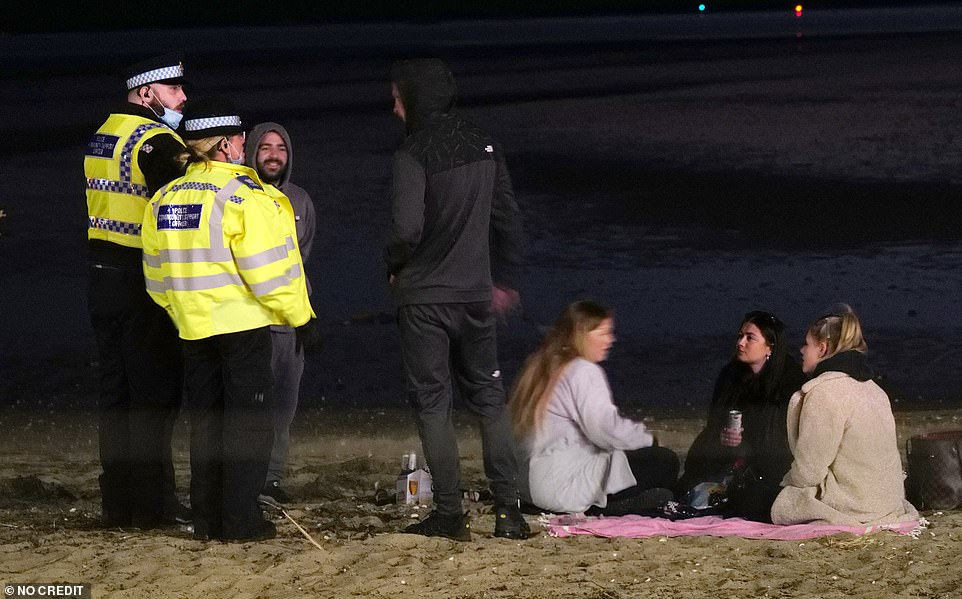 Groups drank on the beach and pavements ignoring social distancing and the police's repeated requests to disperse and go home after a day in the sun in Sandbanks, Dorset, in the early hours of this morning