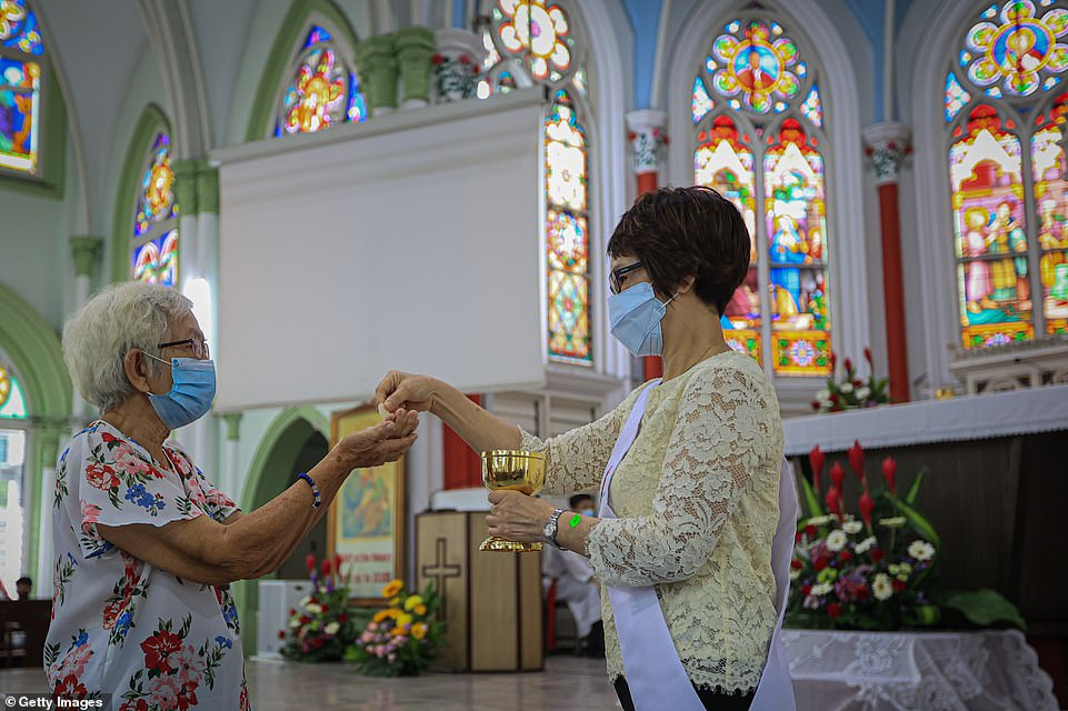 People wear face masks as they attend an Easter Sunday mass service in Kuala Lumpur, Malaysia, amid ongoing Covid restrictions