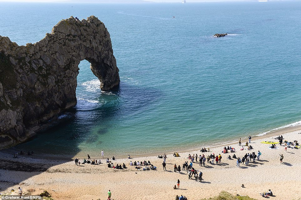 Visitors on the beach looking up to the top of the limestone arch waiting for the base jumpers to leap off. This is the shocking moment two daredevils jumped off the top of the Durdle Door arch using parachutes, Lulworth in Dorset
