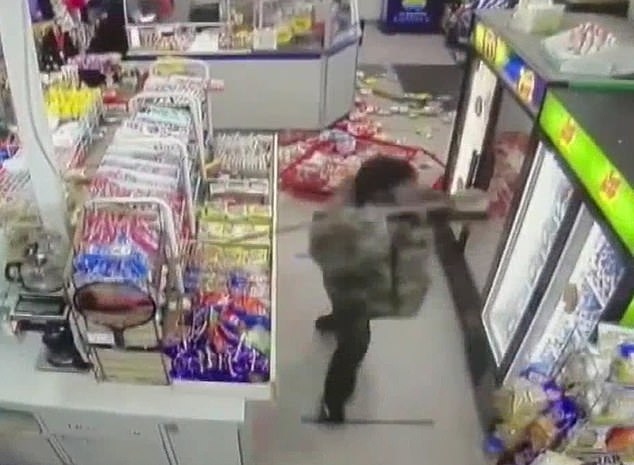 Surveillance footage shot at Plaza Sundries in Charlotte, North Carolina, shows a man pulling a merchandise rack to the floor and shattering refrigerator glass with a street sign post