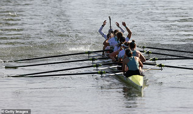 The Cambridge University Women's Boat Club team celebrate victory after crossing the finish line to win during The Gemini Boat Race