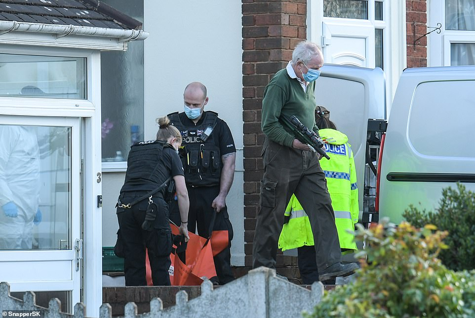 Two armed police officers carry an orange bag holding the body of a dog, followed by a vet holding a tranquilliser gun