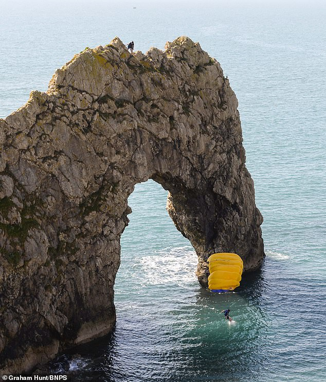 The first man flung himself off and his yellow parachute opened up to control his descent into the chilly sea