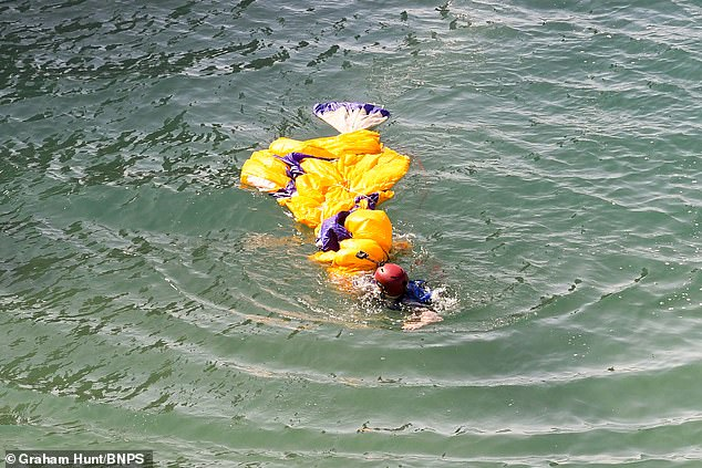 'The first guy who jumped seemed to struggle with his parachute afterwards, it must have been very heavy in the water', a witness said