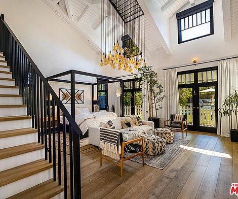 Glass French doors open to the backyard and a high window that makes the most of the two-story room