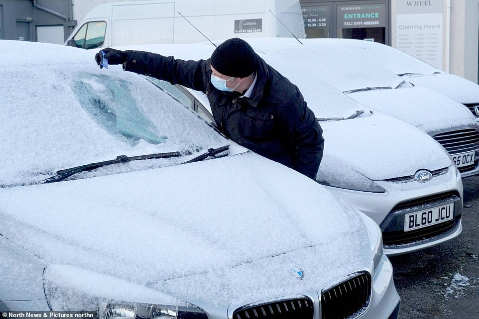 GATESHEAD: A motorist clears snow from a vehicle in Sunniside, Gateshead on Easter Monday following overnight snow
