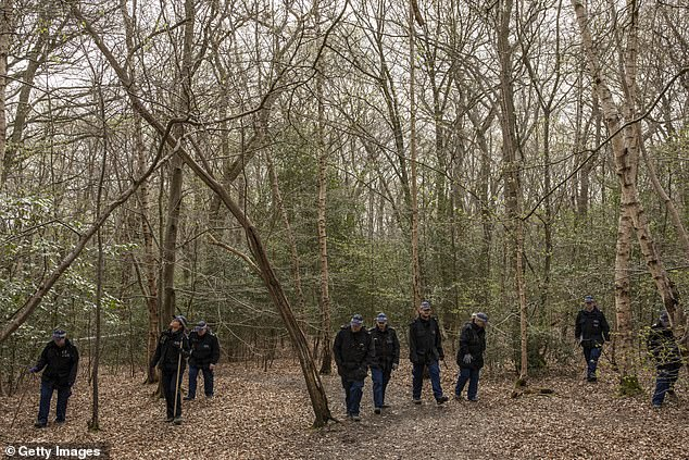 An area is cordoned off as police search teams work their way through woodland in Epping Forest on April 1