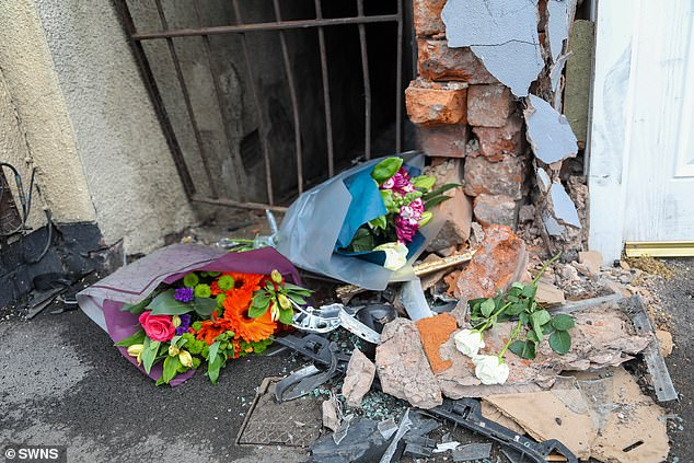 The point at which the car smashed into the shop front, which was marked by flowers left by well-wishers today
