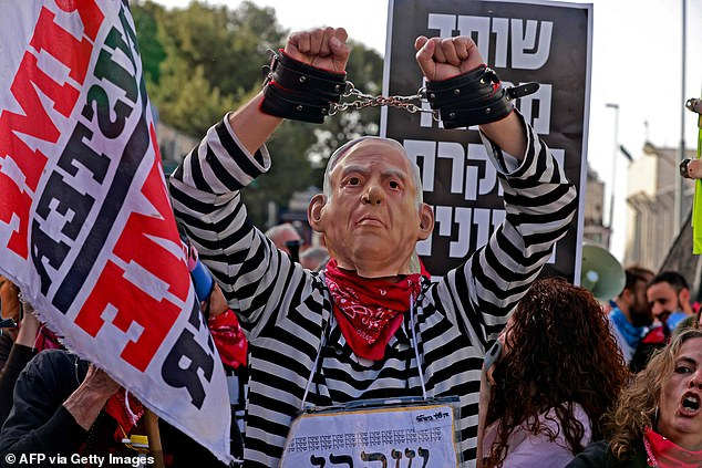 Outside the courtroom, dozens of supporters and opponents of the prime minister gathered to protest on opposite sides of the building amid a heavy police presence, highlighting Israel's deep divisions. Pictured:A protester wearing a mask, depicting Israeli Prime Minister Benjamin Netanyahu, attends a gathering outside the district court in Jerusalem on April 5