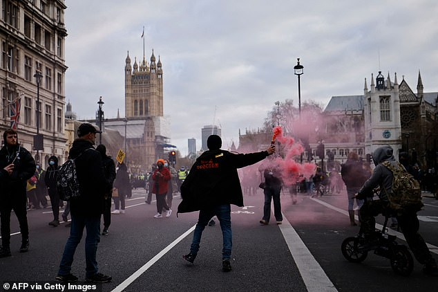 A demonstrator is seen holding a red smoke flare at the 'Kill the Bill' protest n London