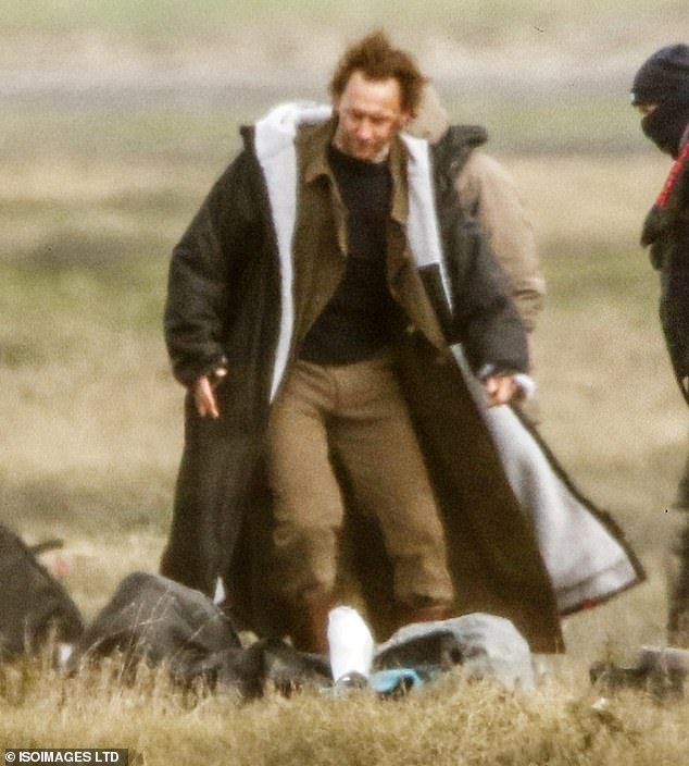 Period drama: Tomsported a dark brown coat along with a black jumper and brown trousers for the shoot