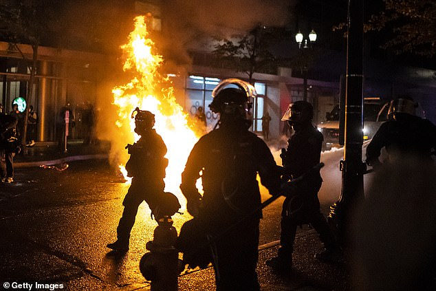 Portland police walk past a fire started by a Molotov cocktail thrown at police