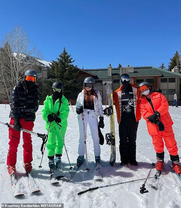 Fun and games: The Barker crew struck a pose while skiing and snowboarding; the Blink 182 drummer is pictured second to the right