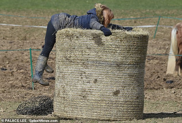 Horsing around! The social media star, 25, bundled up in a navy parka coat and jodhpurs as she tended to several horses and got stuck in to stable duties