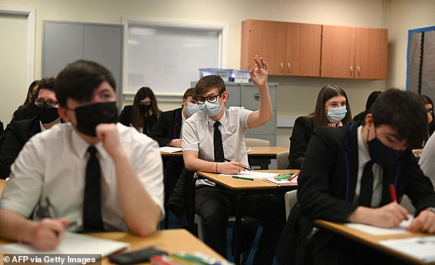 Year 11 students, wearing face coverings, take part in a GCSE maths class at Park Lane Academy in Halifax, northwest England on March 8, 2021