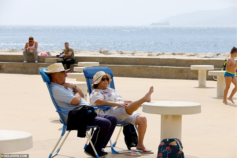 Retired caretaker Adolfo Mor, 76, relaxing on the promenade with his wife Victoria on foldaway chairs (pictured), said: 'This is paradise. 'I'm sitting here enjoying the sunshine and breathing in fresh air without a face mask on'