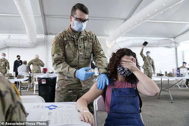 Leanne Montenegro, 21, covers her eyes as she doesn't like the sight of needles, while she receives the Pfizer vaccine at a FEMA vaccination center at Miami Dade College in Miami