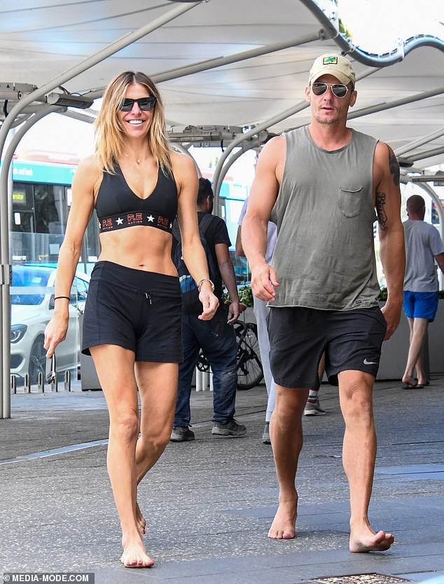 ABS-olutely ripped! Laura Csortan, 44, showed off her washboard abs in a sports bra and shorts as she caught up with a muscly male friend in Bondi on Tuesday