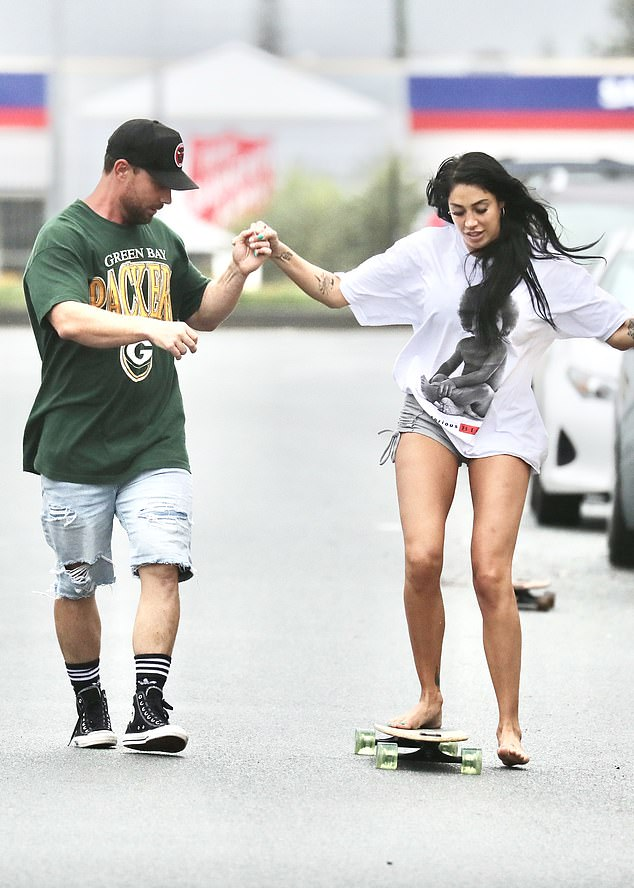 The look: She wore an oversized white T-shirt as Jason held her hands while she balanced atop the skateboard