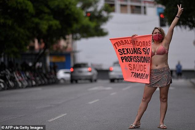 Le gouvernement brésilien a donné la priorité aux agents de santé, aux enseignants, aux personnes âgées, aux autochtones et aux personnes souffrant de problèmes de santé sous-jacents pour la première série de vaccinations.  Sur la photo: une travailleuse du sexe tient une pancarte disant: `` Les travailleuses du sexe sont aussi des professionnelles de la santé '' lors d'une manifestation