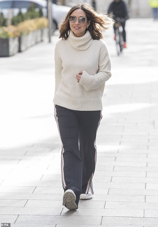 Walk this way: Opting for comfortable footwear, Myleene sported white trainers but added a touch of glamour with oversized tinted shades and dangling earrings