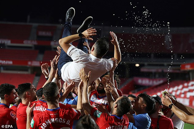 Martinez is thrown into the air by his squad after their Europa League place was confirmed