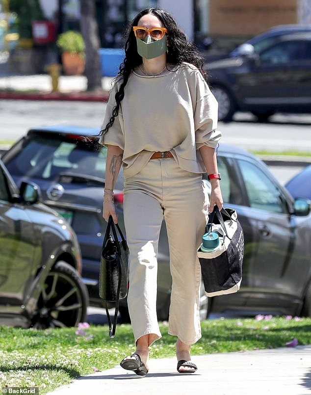 Mask on: The 32-year-old actress and singer wore a plain tan sweatshirt along with matching trousers while headed to a hair salon