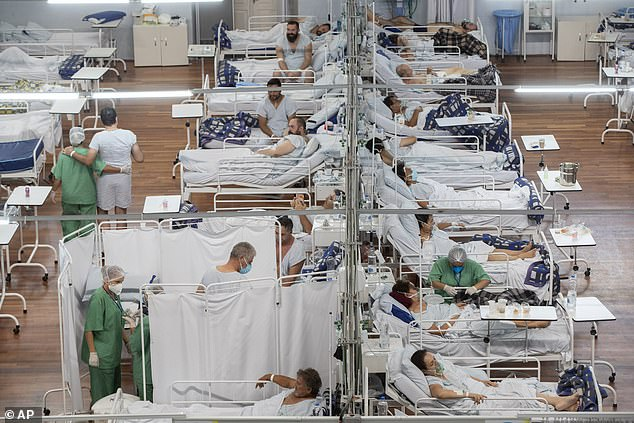 Covid patients lie in beds on a field hospital built inside a sports centre on the outskirts of Sao Paulo