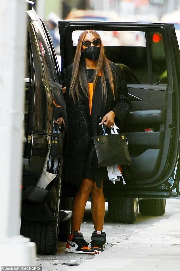 No stopping her:Naomi did not let the pandemic stop her from looking her best as she stepped out in a textured black coat, orange frock, and coordinating Nike sneakers