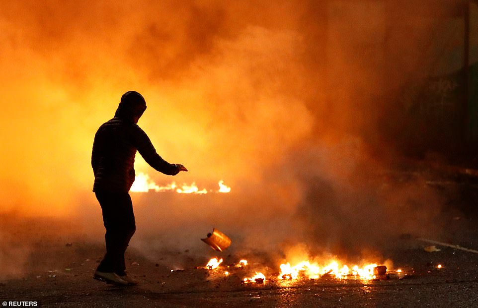 An Irish nationalist stands in smoke close to a fire at the 'peace wall' gates into Lanark Way as protests continued in Belfast, Northern Ireland, last night