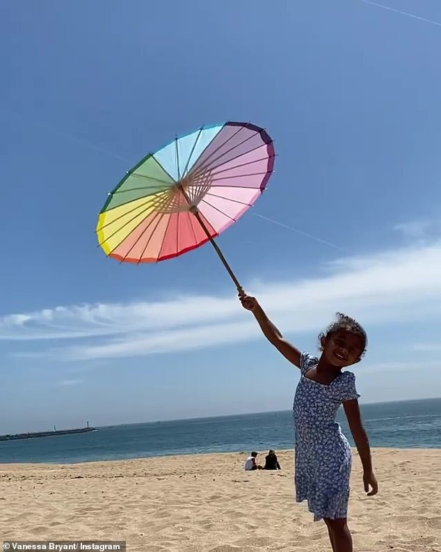 Not a kite:She then turned the camera on her older daughter Bianka, who held up a parasol and said, 'I'm flying a kite!' though her mom corrected her, 'That's not a kite'