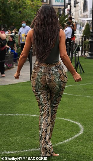 Work it: Kim posed for a slew of snapshots in front of a giant SKIMS backdrop upon arrival
