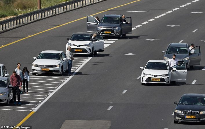 Israelis pause by their vehicles in the main highway leading to Jerusalem on April 8, 2021 as sirens wail across Israel for two minutes marking the annual day of remembrance for the six million Jewish victims of the Nazi genocide