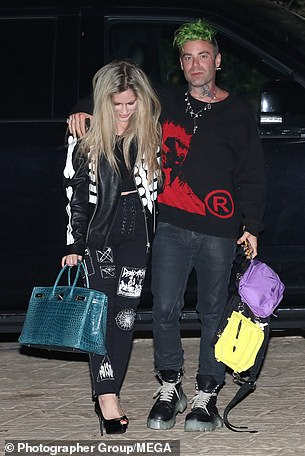 Rocker: Avril put on a chic and casual display by sporting a black biker jacket embellished with bone down the sleeves over a matching shirt