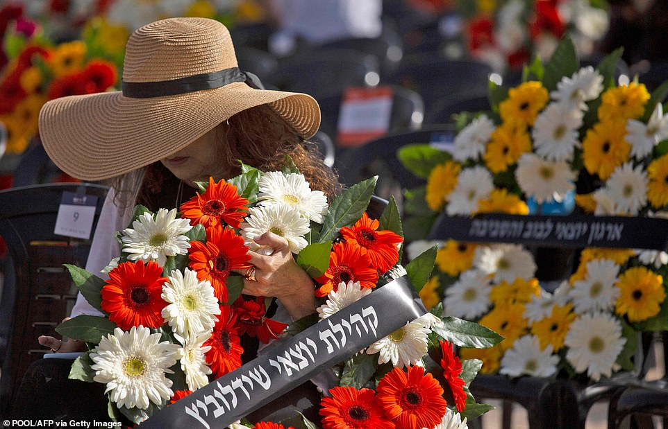 A woman holds a wreath at a ceremony marking the annual Holocaust Remembrance Day at Yad Vashem Holocaust Memorial in Jerusalem, on April 8, 2021