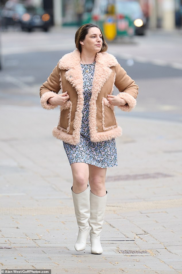 Sixties siren: The Heart FM presenter looked radiant as she flashed a bit of leg walking through the city in knee high white boots