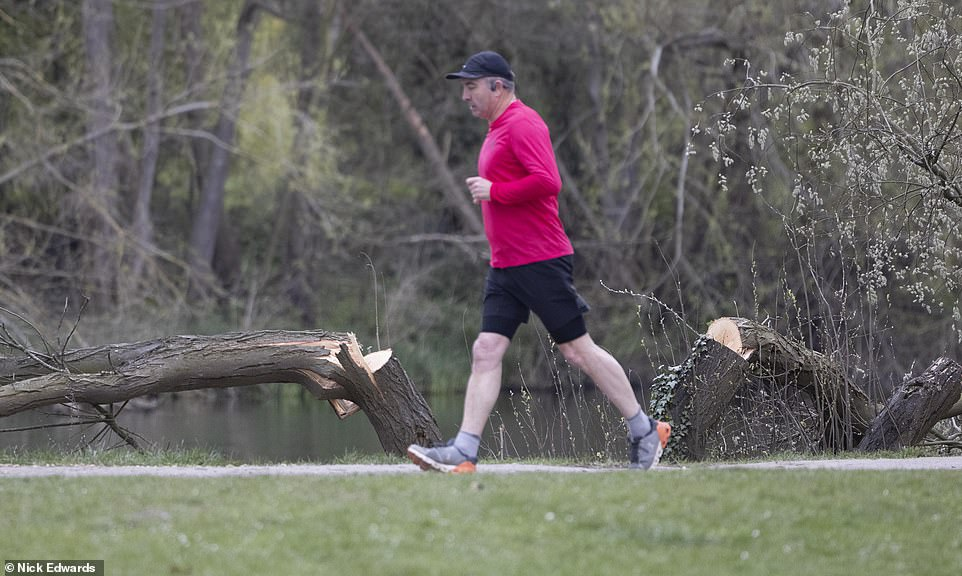 A jogger runs past the scene of one of the attacks by the phantom lumberjack in picturesque Walton-on-Thames in Surrey