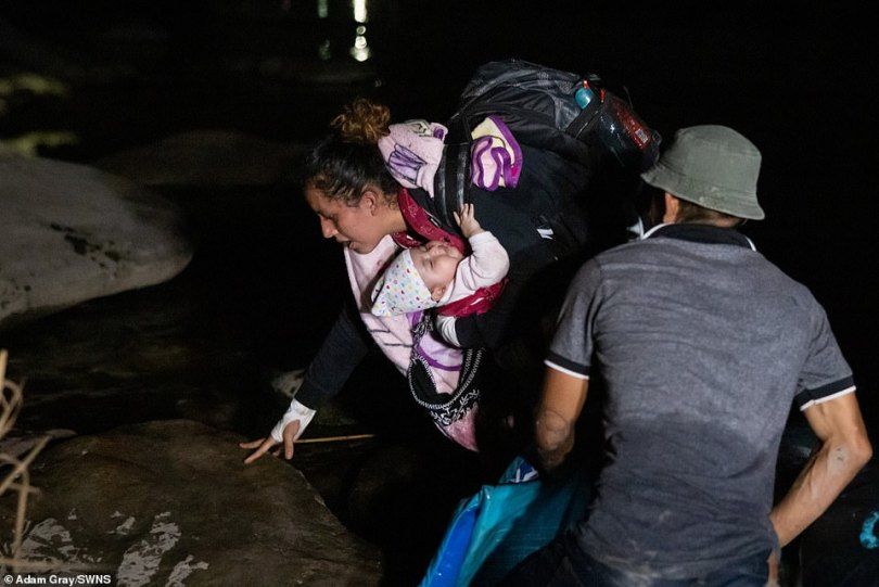 Guatemalan migrant Ceidy, 31, and her 3 month old baby Bridget touch land after crossing the Rio Grande from Mexico on Wednesday